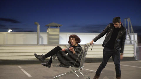 Cute guy in jacket pulls another guy dressed like woman sitting in shopping cart Footage