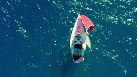 Aerial view. Beautiful sailing yacht with a red sail is sailing on the emerald Live Action