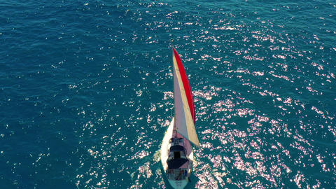Yacht sailing on open sea at sunny day. Sailing boat with a red sail Live Action