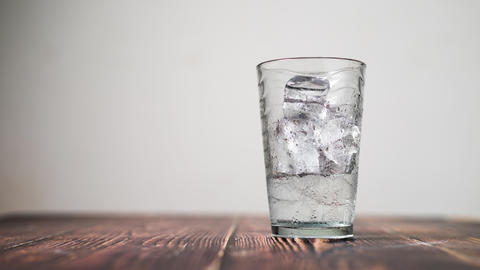 Time lapse shot the ice dissolving in a clear glass on wooden table select focus shallow depth of ライブ動画