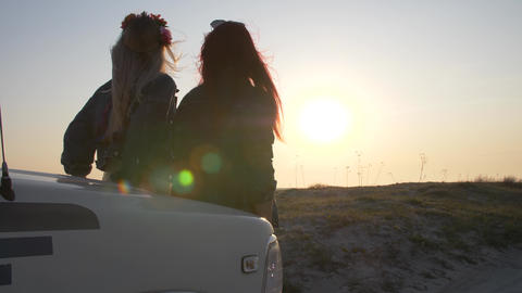 Couple of young women is sitting on the bumper and enjoy the sunset Footage