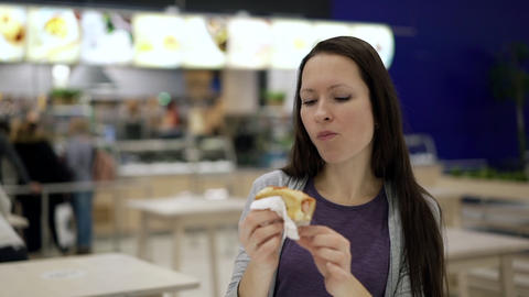 Hungry woman eating at food court in shopping mall. Young pretty woman chewing Footage
