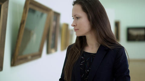 Elegant Beautiful Woman Looks at the Pictures in the Museum of Modern Art. Close Footage
