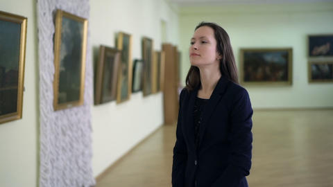 Elegant Girl Looks at the Pictures in the Museum of Modern Art. Young Woman Footage