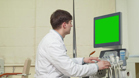 Young male doctor using ultrasound scanner with green screen Live Action