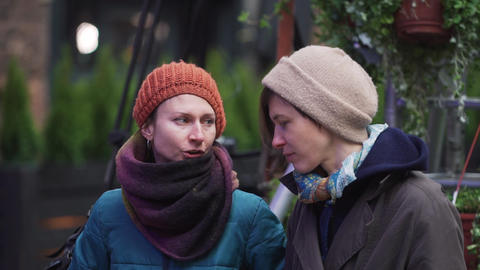 Two mature caucasian women wearing hats and jackets stand outside and talk Footage