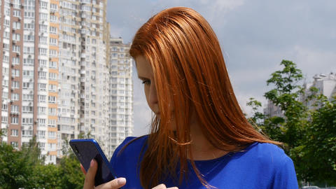 Young beautiful girl with red hair in the city looking for information in a Live Action