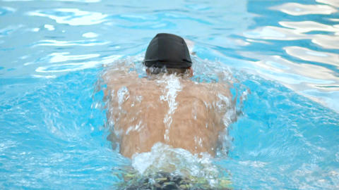 Male swimmer doing butterfly stroke during training in swimming pool, Slow Archivo