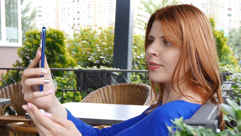 Close-up scene of a charming girl with red hair who is making a selfie in the Footage