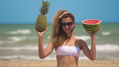 Young beautiful girl has fun at the beach near sea dancing with tropical fruit Footage