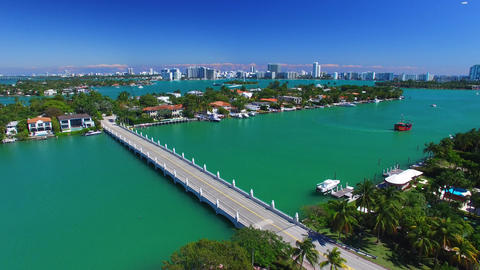 Aerial view of Palm Island and Miami with red cruise boat in canal Footage