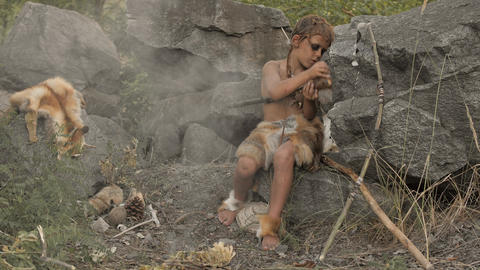 Caveman, manly boy making primitive stone weapon in camp Live Action