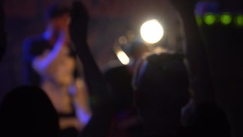Blurred image of dancing and clapping silhouettes of people at a rock concert in Footage