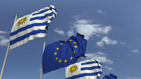 Flags of Uruguay and the European Union against blue sky, loopable 3D animation Footage
