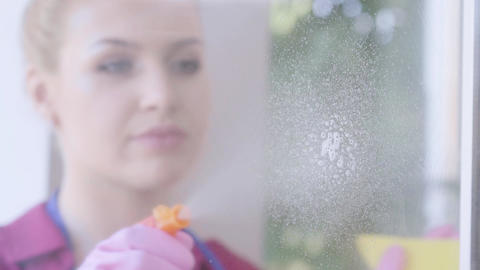 Close-up face of pretty smiling blond girl washing the window with window rag in Footage