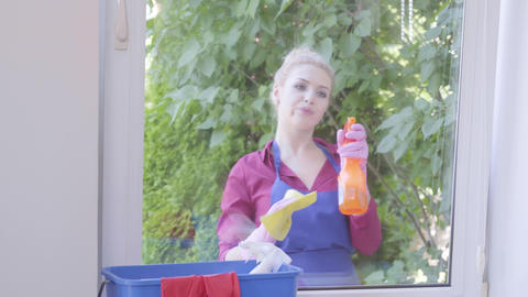 Portrait adorable blond girl in blue apron washing the window with window rag in Footage
