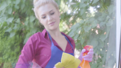 Portrait adorable blond young woman in blue apron washing the window with window Footage
