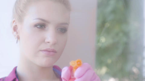 Close-up face of tired blond young woman washing the window with window rag in Footage