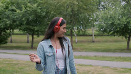 beautiful cheerful girl dancing in the park listening to music on headphones Footage
