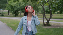 Funny cheerful girl dancing in the park near the trees listening to music on Footage
