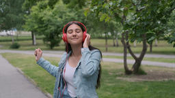 Funny cheerful girl dancing in the park near the trees listening to cheerful Footage