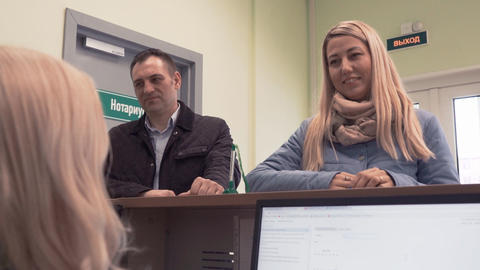 Man and woman listens to manager behind desk in bank building Footage