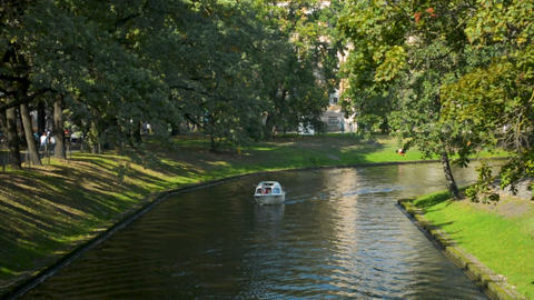 Small river channel ferry transporting tourists in Riga city center in a sunny Footage