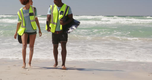 Front view of African american volunteers with garbage bag walking together on the beach 4k Live Action
