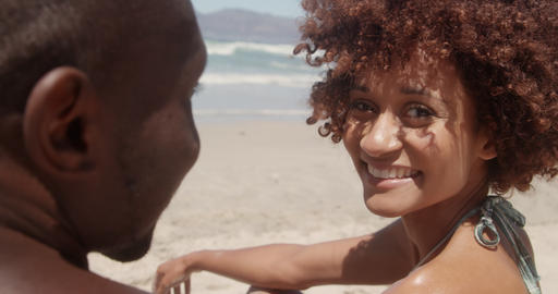 Woman looking at camera on beach in the sunshine 4k Live Action