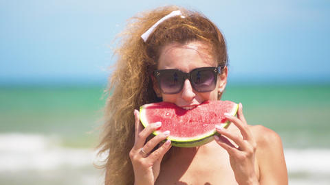Smiling woman eating watermelon on beach. Woman eating tasty summer fruit. Happy Footage