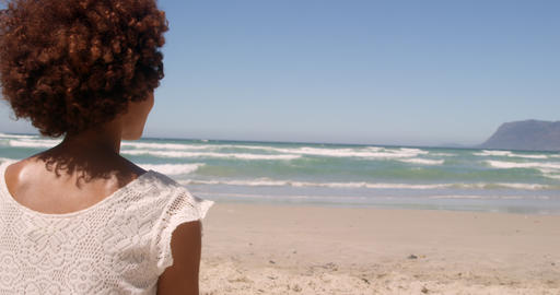 Rear view of young African american woman relaxing on beach in the sunshine 4k Live Action
