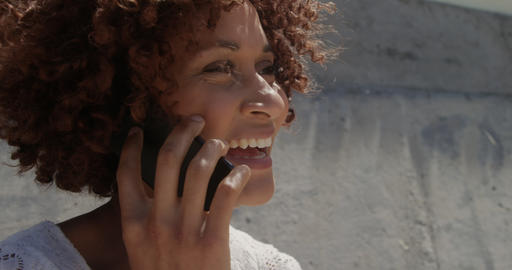 Side view of young African american woman talking on mobile phone at beach in the sunshine 4k Live Action