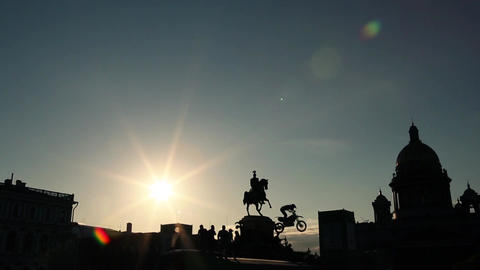 Silhouettes of monument, bunch of people underneath and extreme jumping bikers Footage