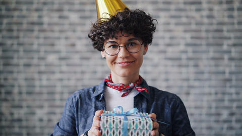 Pretty girl in party hat stretching arms with gift box smiling looking at camera Footage