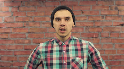 Young blogger in black hat, plaid shirt pronounce words in camera. Brick wall on Live Action