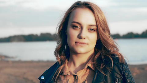 Pretty girl in a black jacket standing near the river Footage