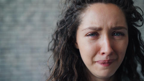 Close-up portrait of unhappy young girl crying on brick wall background Live Action