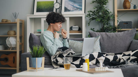 Woman with sore throat using laptop looking for information about disease Footage