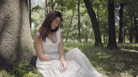 Portrait of cute young girl with long brunette hair wearing a long white summer Live Action