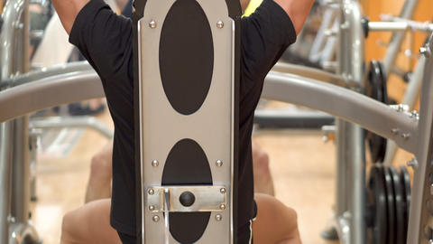 A young fit man does overhead presses in a gym closeup from behind Footage