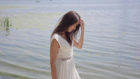 Portrait charming young girl with long brunette hair wearing a long white summer Live Action