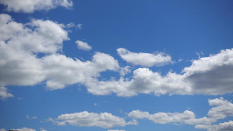 Cumulus clouds move fast across the blue sky, Timelapse. White fluffy clouds in Live Action