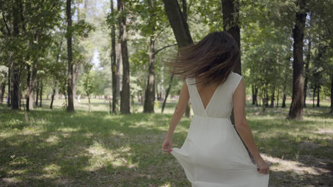 Charming young girl dressed in a white long summer dress spin in the park Footage