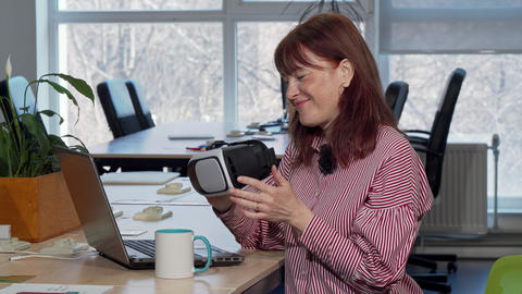 Mature businesswoman enjoying using virtual reality headset at her workplace Live Action