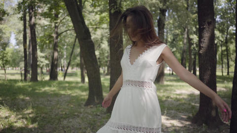 Adorable young girl dressed in a white long summer dress spin in the park Footage