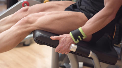 Close-up view of the man athlete with muscular legs working out at the gym leg Live Action