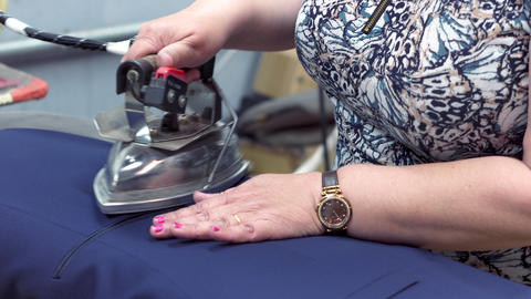 Close-up: A seamstress woman steams a jacket using an old-fashioned iron. A Footage