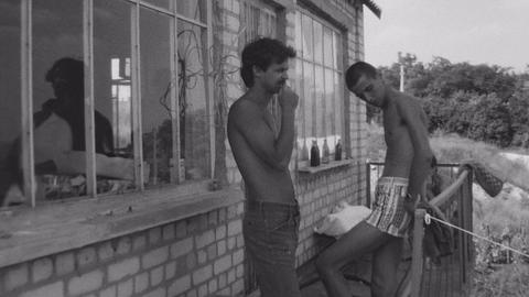 DONETSK, UKRAINE, 1986: Old vintage black and white film two young man chilling Live Action