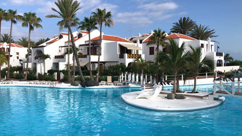 Swimming pool in tropical hotel resort with palm trees for beach holidays Acción en vivo