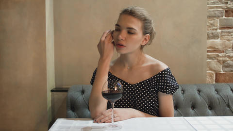 Portrait of a young woman in an evening dress in a restaurant with glass of wine Live Action